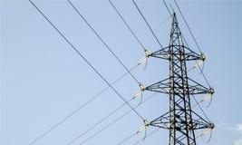Polo eletric da tensão grande da altura na luz - fundo do céu azul, corrente elétrica, fios fotografia de stock