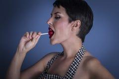 Polo, mujer joven feliz con el lollypop en su boca en el CCB azul Foto de archivo