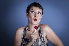 Polo, mujer joven feliz con el lollypop en su boca en el CCB azul Fotografía de archivo libre de regalías