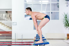Polo player, athlete and swimmer getting ready to jump in indoor pool Stock Image