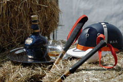 Polo player helmet, polo mallets, and whiskey. Tseleevo, Moscow region, Russia - July 26, 2014: Equestrian helmet, polo mallets, and a bottle of Scotch whiskey Royalty Free Stock Images
