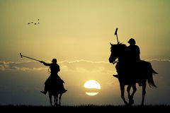 Polo players at sunset Royalty Free Stock Photo