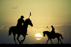Polo players at sunset Stock Images