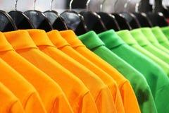Polo Shirts. Hanging Orange and Green Polo Shirts Stock Image