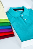 Polo shirts. Luxurious fine material 100% cotton polo shirt displayed in a gift box with a pile of another polo shirts in many different colors Stock Image