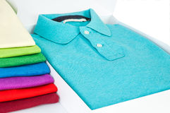 Polo shirts. Luxurious fine material 100% cotton polo shirt displayed in gift box with a pile of another polo shirts in many different colors Stock Photography
