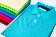 Polo shirts. Luxurious fine material 100% cotton polo shirt displayed in a gift box with a pile of another polo shirts in many different colors Royalty Free Stock Images