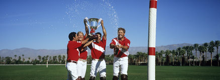 Polo team celebrating with trophy on field royalty free stock image