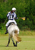 Polocrosse player on horse, back view Royalty Free Stock Images