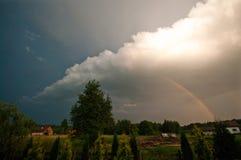 Polonia rural, región de Ilawa, arco iris sobre el pueblo de Sapy Imagenes de archivo