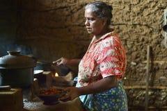 Polonnaruwa,斯里兰卡, 2015年11月8日:准备食物的Sri Lankian老妇人在厨房里用传统方式 图库摄影