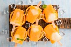 Polos congelados hechos en casa del helado hechos con las naranjas frescas oragnic en fondo de madera Fotografía de archivo libre de regalías