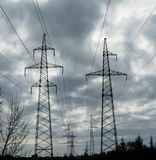Polos da eletricidade do poder superior na área urbana Fotografia de Stock