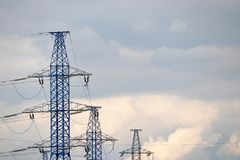 Polos de alta tensão da linha elétrica com fios elétricos no fundo de nivelar o céu com nuvens imagem de stock