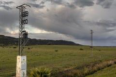 Polos de alto voltaje en un paisaje verde de la naturaleza imágenes de archivo libres de regalías