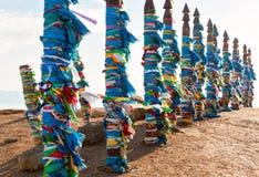 Polos de madeira tradicionais à sarja do cargo engatando Bandeiras da oração em Olkhon, região de Buryat, Rússia, Sibéria Imagens de Stock