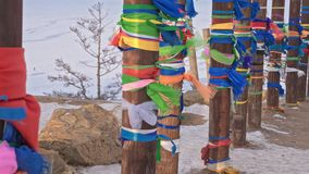 Polos rituales budistas con las cintas coloreadas en el invierno en el lugar santo del lago Baikal Lugar sagrado… Polos de madera almacen de video
