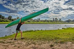 One young athlete leaves of river with canoe on shoulders. Royalty Free Stock Photos