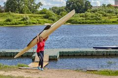 One girl sportswoman bears kayak on shoulder, Polotsk, Belarus. Royalty Free Stock Images