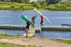 Teens carry canoe on their shoulders after training in rowing. Royalty Free Stock Photo