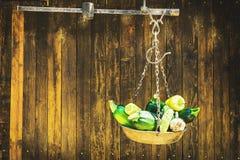 Polpa e alho de abóbora verde que penduram na escala de feixe do metal na frente da porta rústica de madeira, no espaço para o te imagens de stock royalty free