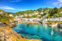 Polperro Cornwall England uk with clear blue and turquoise sea in vivid colour HDR like painting. Beautiful Polperro harbour Cornwall England with clear blue and Royalty Free Stock Photography