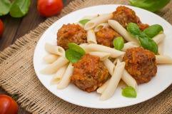 Polpette con il penne della pasta in salsa al pomodoro su un piatto bianco Priorità bassa rustica di legno Vista superiore Primo  Immagini Stock Libere da Diritti