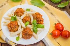 Polpette con il penne della pasta in salsa al pomodoro su un piatto bianco Priorità bassa rustica di legno Vista superiore Primo  Fotografie Stock