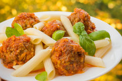 Polpette con il penne della pasta in salsa al pomodoro su un piatto bianco Priorità bassa rustica di legno Vista superiore Primo  Fotografia Stock