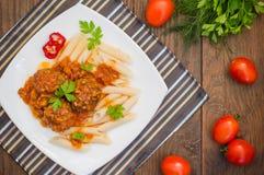 Polpette con il penne della pasta in salsa al pomodoro su un piatto bianco Priorità bassa rustica di legno Vista superiore Primo  Immagine Stock
