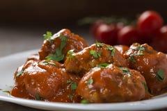 Polpette con salsa al pomodoro e prezzemolo tagliato fresco sul piatto Fotografie Stock
