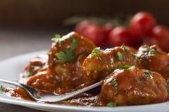 Polpette con salsa al pomodoro e prezzemolo tagliato fresco sul piatto Fotografia Stock