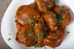 Polpette con salsa al pomodoro e prezzemolo tagliato fresco sul piatto Immagini Stock