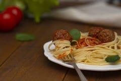 Polpette della pasta degli spaghetti con salsa al pomodoro, basilico, parmigiano delle erbe su fondo di legno immagine stock