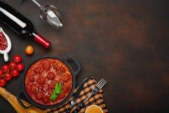 Polpette in salsa al pomodoro con le spezie, i pomodori ciliegia, la pasta ed il basilico in una padella con la bottiglia di vino immagini stock
