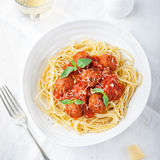 Polpette in salsa al pomodoro ed in basilico fresco con gli spaghetti su una vista superiore del piatto bianco Fotografie Stock Libere da Diritti