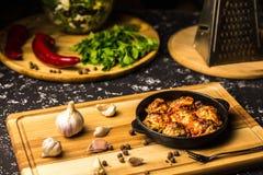 Polpette in una pentola del ferro su un bordo di legno con aglio ed i granelli di pepe fotografia stock
