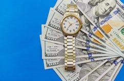 Polshorloge op dollars op blauwe dichte omhooggaand als achtergrond royalty-vrije stock afbeelding