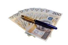 Polsk pengarlön och en penna Arkivbilder