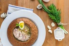 Polsk rågsoppa med ägg och korven i bröd arkivbild