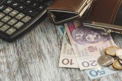 Polski złoty z małymi portflami i kalkulatorem na drewnianym tle obraz stock