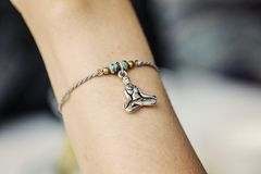 Polso femminile che indossa il braccialetto minuscolo dei gioielli immagine stock