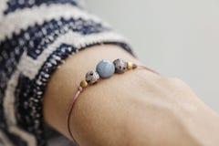 Polso femminile che indossa il braccialetto minuscolo dei gioielli immagini stock