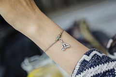 Polso femminile che indossa il braccialetto minuscolo dei gioielli immagine stock libera da diritti
