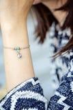 Polso femminile che indossa il braccialetto minuscolo dei gioielli fotografia stock libera da diritti
