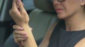 Polso scaldantesi femminile dopo il giorno del grosso lavoro, sedentesi in automobile, auto-massaggio archivi video