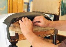 Polsterer, der den Sitz eines Stuhls repariert Lizenzfreies Stockfoto