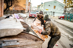 POLTAVA, DE OEKRAÏNE - 18 FEBRUARI 2016: Twee jonge mensen dichtbij de vuilnisbak die document voor recycling verzamelen Stock Afbeeldingen