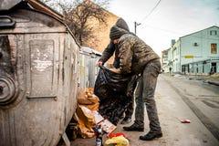 POLTAVA, DE OEKRAÏNE - 18 FEBRUARI 2016: Twee jonge mensen dichtbij de vuilnisbak die document voor recycling verzamelen Royalty-vrije Stock Afbeelding