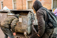 POLTAVA, UCRANIA - 18 DE FEBRERO DE 2016: Dos hombres jovenes cerca del cubo de la basura que recogen el papel para reciclar Fotografía de archivo libre de regalías